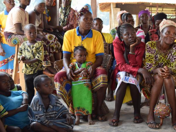 Beneficiaries from TCDO sitting and listening to a speaker with their children