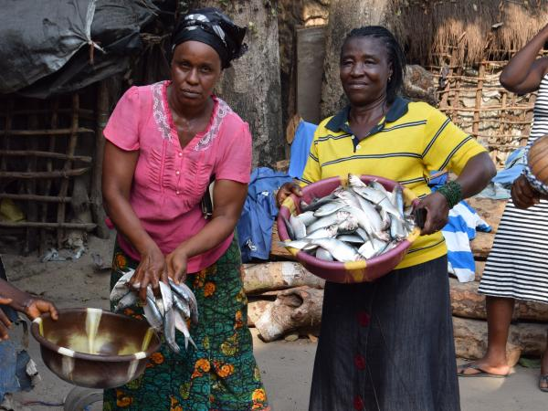 Two GCDF beneficiaries holding baskets of fish