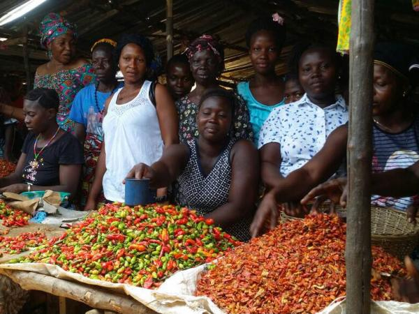 Women in Sierra Leone in front of a market stall with piles of peppers