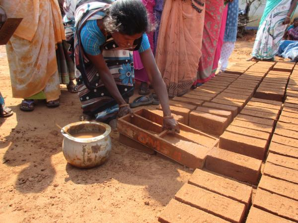 Woman from WVT making bricks