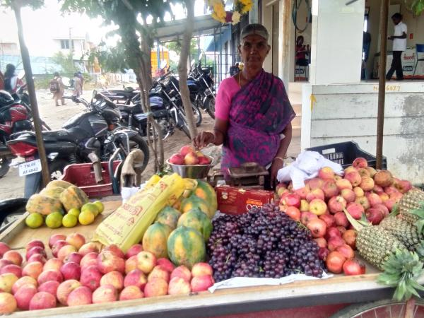 An image of a woman standing behind a fruit stall