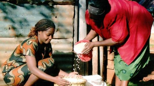 Two Kenyan women pouring grain