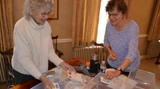 Linda Lee and Amy Perry of FFI sorting stamps